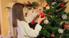 Portrait of cute girl in sweater decorating Christmas tree with baubles Stock Footage