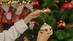 Closeup shot of young woman decorating Christmas tree with baubles Stock Footage