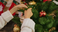 Closeup of girl decorating Christmas tree. Camera zooms in from hands to baub Stock Footage