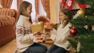 Portrait of two cheerful girl receiving Christmas gifts and hugging each othe Stock Footage