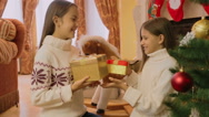 Two cheerful girls receiving Christmas gifts at morning Stock Footage