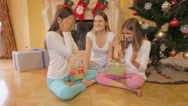 Young beautiful woman sitting with daughters under Christmas tree and giving Stock Footage