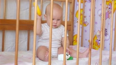 Beautiful baby girl sitting in bed and holding a toy Stock Footage