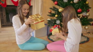 Two girls in pajamas going in living room and taking Christmas gifts Stock Footage