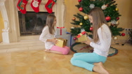 Two happy girls in pajamas taking Christmas gifts and opening them Stock Footage