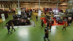 Lot of people walk by antique vehicle exhibition area. Aerial view Stock Footage