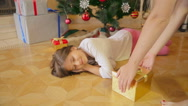 10 years old girl sleeping under Christmas tree at morning. Mother leaving pr Stock Footage