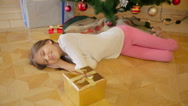 Mother giving Christmas gift to her girl that fell asleep on floor at living Stock Footage