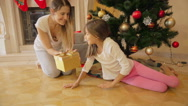 Mother waking her daughter that felt asleep under Christmas tree and giving h Stock Footage