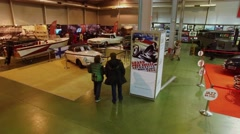 Antiquated vehicle flaunted on exhibition area with people. Aerial view Stock Footage