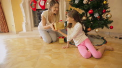 Cute girl fell asleep under Christmas tree. Mother waking her and giving Chri Stock Footage
