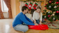 Happy smiling parents with daughter wrapping present for Christmas Stock Footage