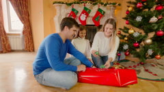 Happy family sitting on floor and wrapping Christmas presents in paper and de Stock Footage