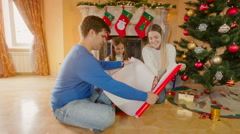 Happy family with girl wrapping Christmas gifts in red wrapping paper Stock Footage
