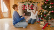 Happy young couple decorating Christmas tree and throwing tinsel at each othe Stock Footage