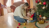 Young mother playing with baby boy under Christmas tree at living room Stock Footage