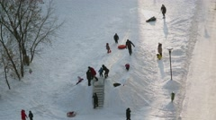 Many people with kids play on snow coast at winter evening. Timelapse Stock Footage
