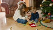 Cute girl playing with her little brother on floor under Christmas tree Stock Footage