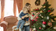 Happy young mother holding baby boy on hands and showing him Christmas tree. Stock Footage