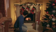 Young man inflaming fire in fireplace at living room decorated for Christmas Stock Footage