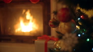 Closeup image of golden and red baubles on Christmas tree. Burning fireplace  Stock Footage