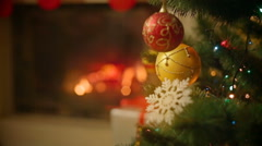 Closeup image of beautiful decorated Christmas tree in front of burning firep Stock Footage