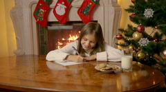 Beautiful 10 year old girl writing letter to Santa Claus with wishes Stock Footage