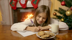 Portrait of cute smiling girl sitting behind table at living room and writing Stock Footage