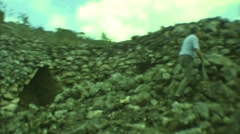 1973: man climbs steep, rugged cliff face upwards towards ledge very slowly Stock Footage