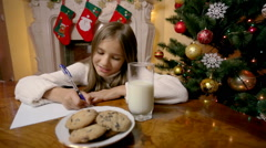 Dolly shot of cute girl writing letter to santa at living room with fireplace Stock Footage