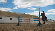 Young woman jumps horse over an obstacle during her training in an arena Stock Footage