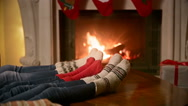 Family with child in knitted woolen socks warming at burning fireplace at hou Stock Footage