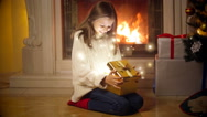 Cute girl in sweater opening magical Christmas gift box. Light and sparkles f Stock Footage