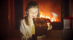 Portrait of excited girl looking inside of Christmas gift box. Magic dust and Stock Footage