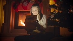 Dolly zoom in shot of excited 10 years old girl opening Christmas present Stock Footage