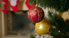 Closeup of beautiful red bauble hanging and spinning on Christmas tree next t Stock Footage