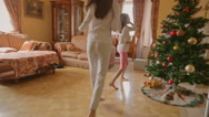 Two cheerful girls in pajamas running to presents under the Christmas tree at Stock Footage