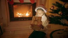 Portrait of happy excited girl sitting at fireplace opens Christmas gift box Stock Footage