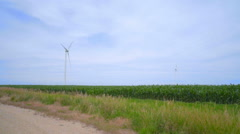 Wind turbines on green field over clouds sky. Alternative energy production Stock Footage