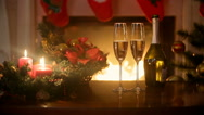 Glasses filled with champagne and burning Christmas candles on table at firep Stock Footage