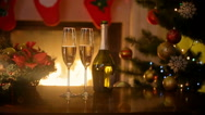 Christmas table with two glasses of champagne lit by burning fireplace at liv Stock Footage