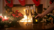 Pouring champagne in two glasses on Christmas dinner table. Burning fireplace Stock Footage