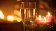 Two glasses of champagne on table in front of burning fireplace at Christmas  Stock Footage