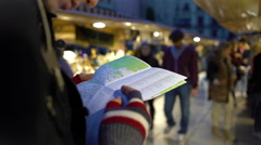 Traveller holding city map in hands, looking at souvenir shops, checking route Stock Footage