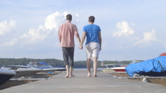 Two Gay Men Walking Hand In Hand Down Pier Stock Footage