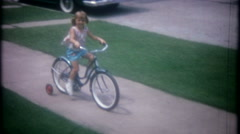 Bicycle trainning wheels helps little girl ride-3623 vintage film home movie Stock Footage