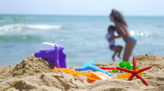 Mother and little son playing at the sea beach, sand toys in front Stock Footage