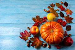 Pumpkin, apples, berries, acorns and fall leaves on blue background copy spac Stock Photos