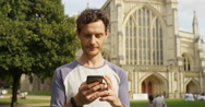 4k, Young attractive man browsing the internet on his touchscreen smart phone.  Stock Footage