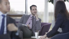 4K Business man & woman in discussion in busy meeting area of modern office Stock Footage